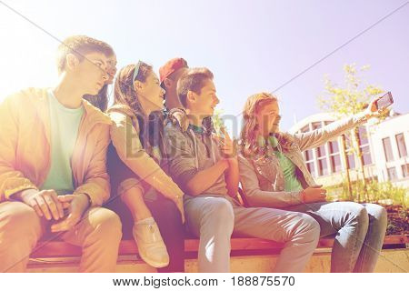 education, high school, technology and people concept - group of happy teenage students or friends taking selfie by smartphone