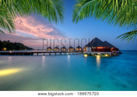 Water villas in lagoon, Maldives resort island in sunset. Detail of palm leaves on foreground. Vacation and beach relaxation, summer holidays background