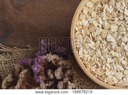 Oat flakes or oatmeal in wood bowl put on rustic wood table. Rolled oat is clean food for health lover people. Prepare oat flakes for bakery or cooking.Natural organic food in vintage style concept.Oat flake, oatmeal background and texture.