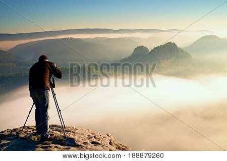 Professional on cliff. Nature photographer takes photos with mirror camera on peak of rock. Dreamy fogy landscape spring orange pink misty sunrise in a beautiful valley below.