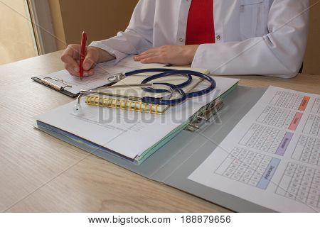 Female medical doctor writing something sitting at her office. Healthcare and medical concept. Medicine doctor's working place