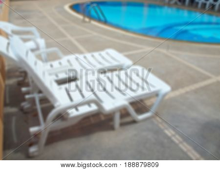Abstract blurred swimming pool with chaise loungue on terrace.