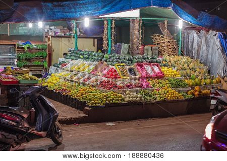A street market of fruits and vegetables in the evening on the main shopping street of Arambol. Goa. India. Abundance of natural vegetarian food.