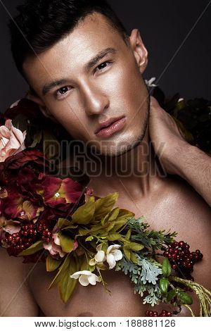 A handsome man with a naked torso, bronze tan and flowers on his body. Photo taken in studio