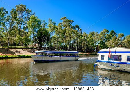 Adelaide Australia - April 14 2017: Iconic Pop-Eye boat with people on board traveling upstream Torrens river in Adelaide CBD on a bright day