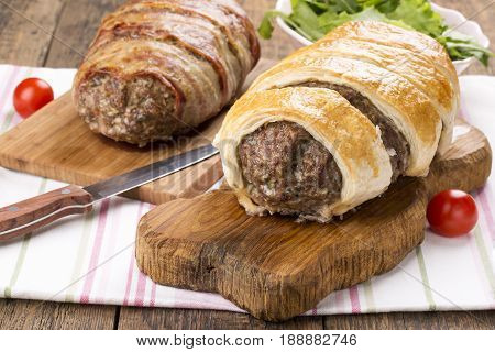 Minced meatloaf wrapped in puff pastry on wooden table