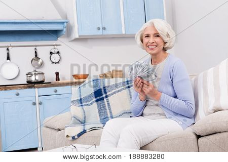 Elderly woman is happy that she has old age. Elderly woman holding much money in her hands while smiling for camera and sitting on sofa or couch.
