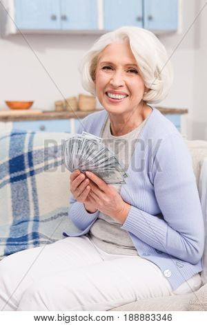 Pensioner received pension and looking happy. Elderly woman holding much money in her hands while sitting on sofa or couch.