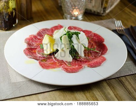 carpaccio con parmesano y rúcula. Carpaccio with parmesan and arugula.