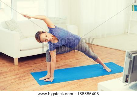 fitness, sport, people and healthy lifestyle concept - woman making yoga bikram triangle pose on mat and watching tv lesson
