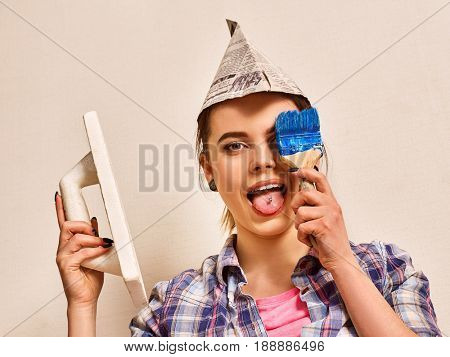 Repair home woman holding paint roller for wallpaper. Female in newspaper cap with brush renovation apartment. Paint bank and roll paper background on isolated. Mad girl with piercing builder.