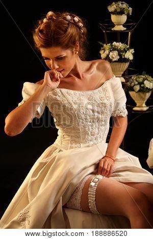 Bride puts bridal garter before wedding ceremony. Candle illuminates and flowers house on black background.