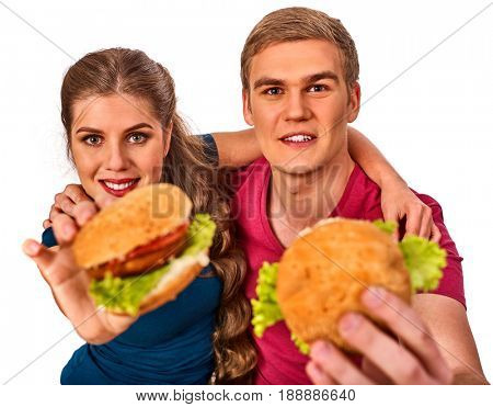 Couple eating fast food. Man and woman treat big hamburger with ham. Friends give burder junk on white background isolated. Beginner chefs and his food semi-finished products.