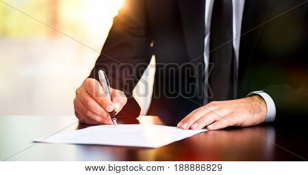 Businessman Signing Legal Document In His Office