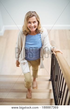 Portrait of smiling senior woman climbing upstairs at home