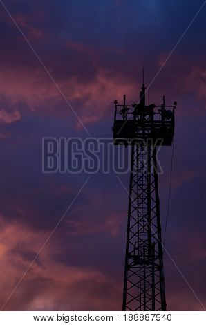 Silhouette mast lighting against the evening sky