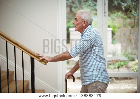 Senior man climbing upstairs with walking stick at home