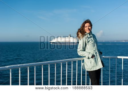 Young traveller woman looking at camera and smiling, on the sea sailing a ferry, with big boat cruise liner or ferry on the background, wearing a rain jacket.