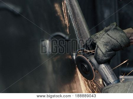Close up of worker's hands polishing metal parts in industrial plant