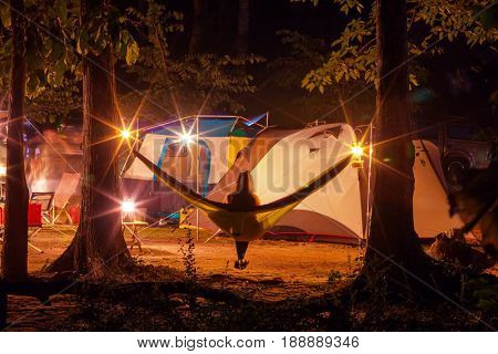 Amazing scene in night camping -girl in hammock on tents background
