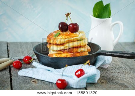 Homemade cottage cheese pancakes with cherries in a cast-iron frying pan. Russian dessert from cottage cheese.