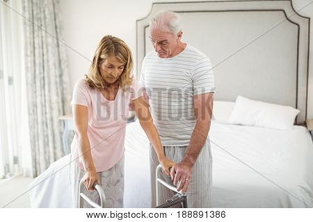 Senior woman helping senior man to walk with walker at home