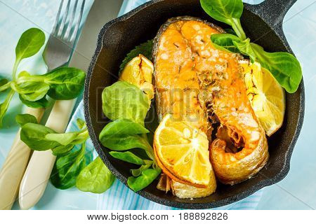 Chum baked with lemon in a cast-iron frying pan.