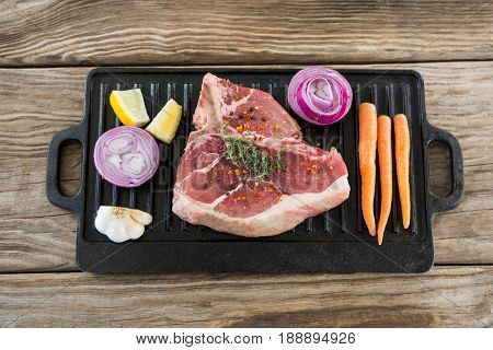 Sirloin chop and ingredients on grill tray against wooden background