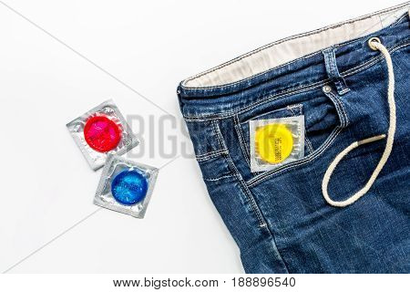 male contraception for safe sex with condoms jeans on white desk background top view