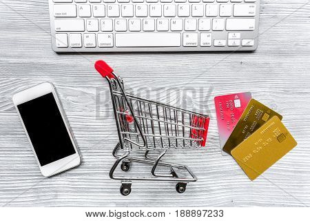 buying products with credit cards, phone and mini trolley on light table background top view space for text
