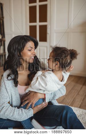 Happy African American Mother Sitting On Floor With Adorable Little Daughter