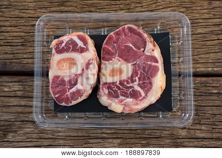 Sirloin chop in plastic box against wooden background