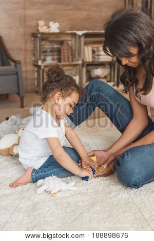 Cute Little Kid Girl Playing Toys With Mother At Home