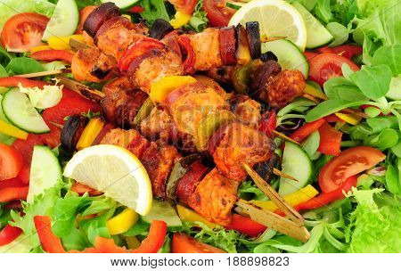 Chicken and spicy chorizo sausage kebabs with sweet peppers on a salad background