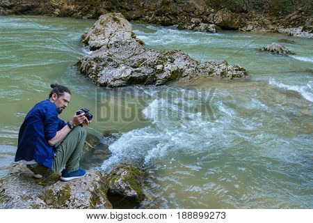 A young guy in a blue shirt shoots a mountain river