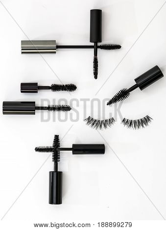 collection of different mascara brushes on a white background. with false eyelashes