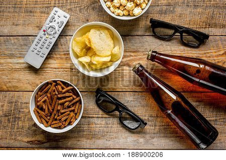 watching TV set with chips, beer and remote control on wooden background top view