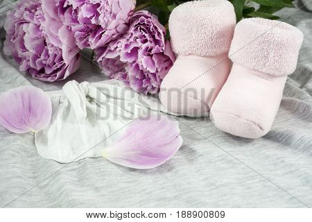 Pair of bootees for newborn girl with several peonies as background