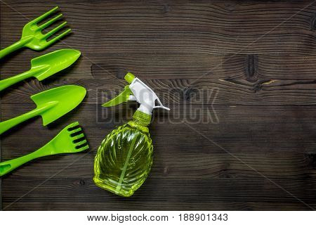 Planting flowers in garden with green instruments on wooden desk background top view mock-up