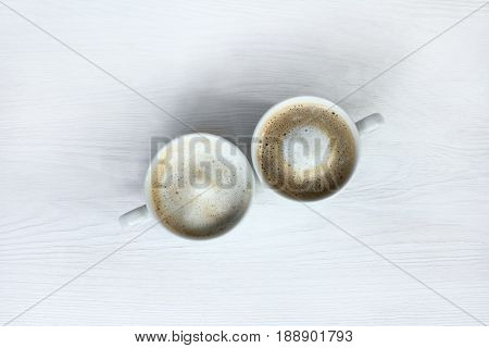 Two white cups with frothy cappuccino on a light table top view / coffee pause for a couple