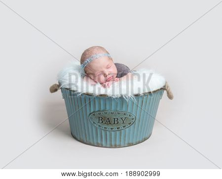 Sweet child napping, dressed in brown knitted suit, in a blue metal basket