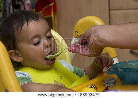 mother feeding baby boy at home kitchen people