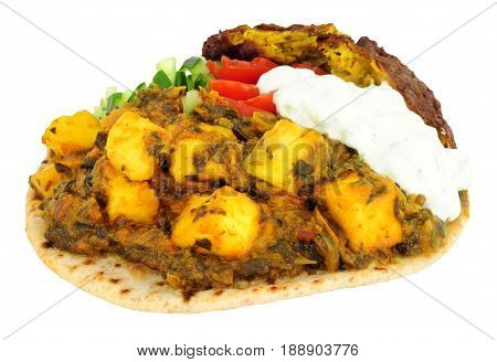 Indian saag paneer cheese meal on a chapati flatbread isolated on a white background