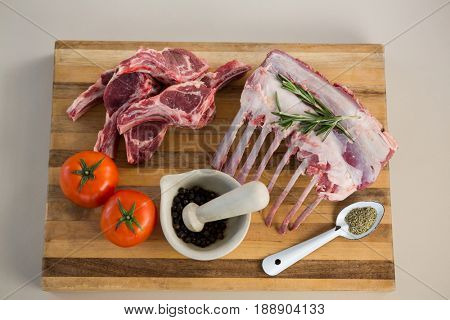 Rib rack, rib chop and ingredients on wooden board against white background