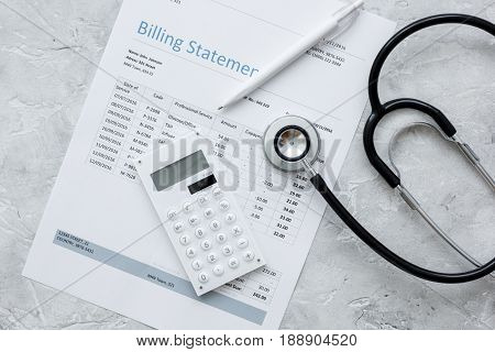 stethoscope, billing statement for doctor's work in medical center on stone background top view