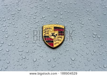 BERLIN - MAY 13 2017: Hood emblem of sports car Porsche in raindrops on the grey background. Exhibition