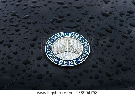 BERLIN - MAY 13 2017: Hood emblem of Mercedes-Benz in raindrops on the dark background. Exhibition