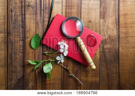 Photo of red notebook magnifier wax seal herry flowers and green leaves on vintage wooden background. Stationery elements.