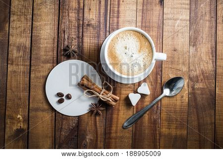 Delicious fresh coffee. Coffee cup with cinnamon sticks coffee beans anise sugar spoon and coasters on vintage wooden kitchen table background. Top view.