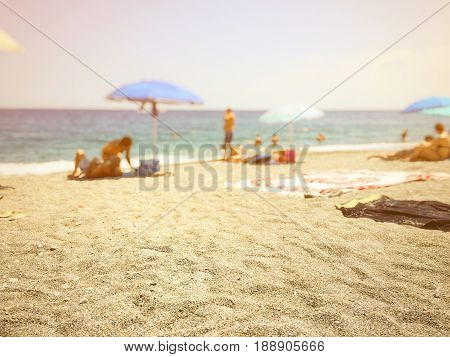 close up of beach sand with blurry people relaxing by the sea in the background